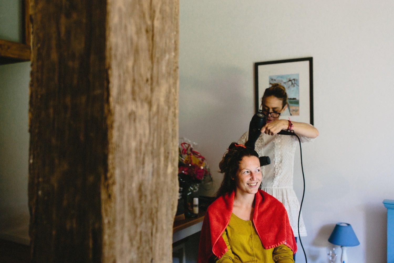 Eine lachende Braut wird von der Friseurin Anja Goldemann vor ihrer Hochzeit gestylt