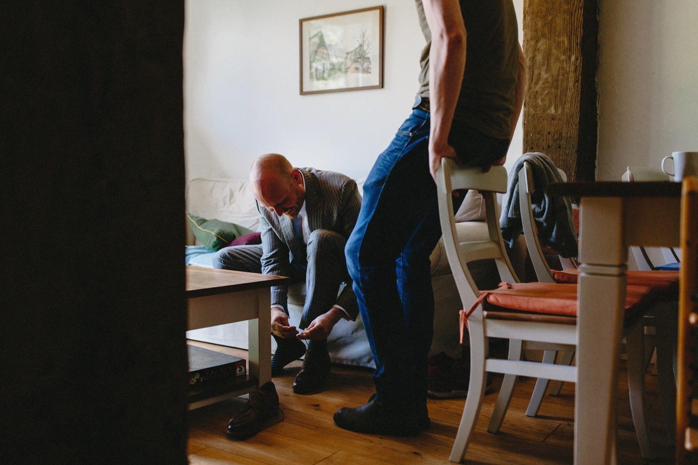 Der Bräutigam lacht und zieht sich im Beisein seines Trauzeugen seine Schuhe an
