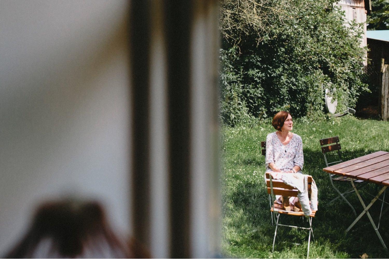 Ein Hochzeitsgast wartet im Garten der Ferienwohnungen auf Hof Eggers auf den Beginn der Trauung