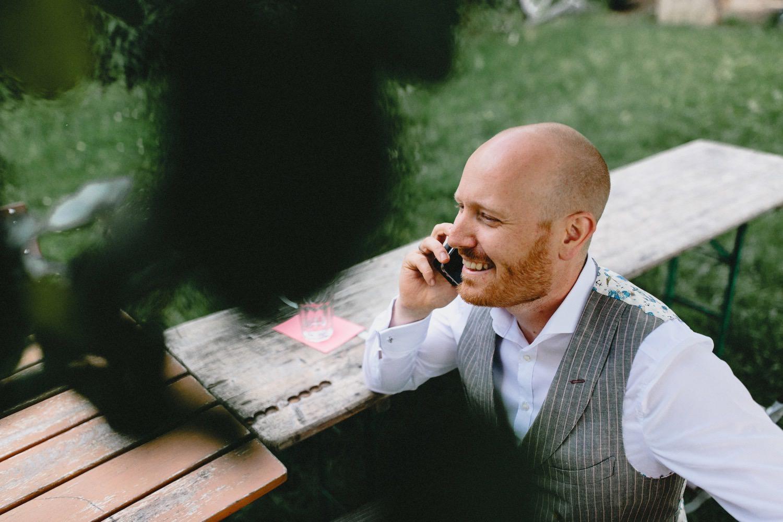 Der Bräutigam telefoniert im Garten von Hof Eggers in Hamburg vor der Trauung auf dem Feld