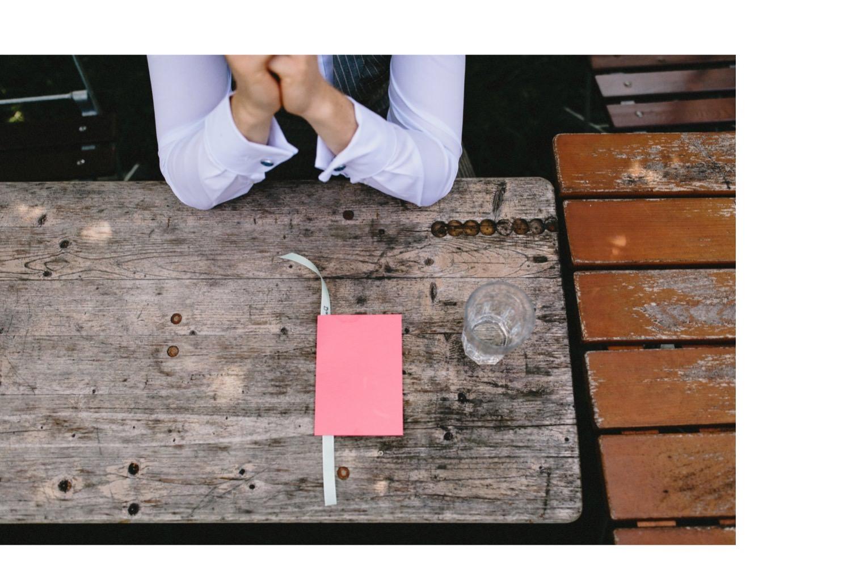 Der Bräutigam sitzt am Tisch und vor ihm liegt sein Eheversprechen in einem rosa Umschlag
