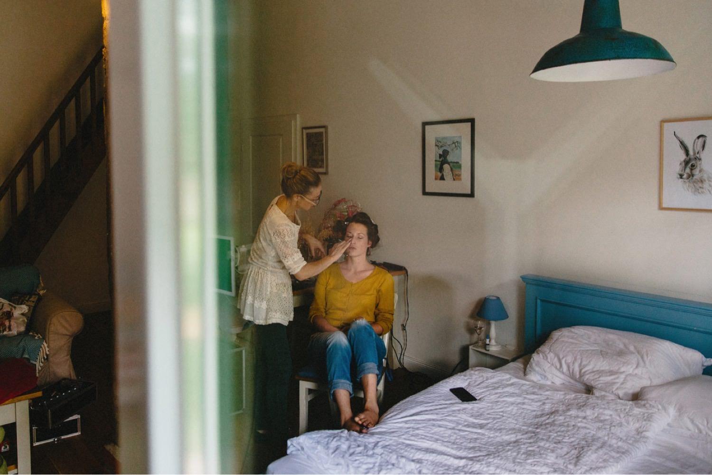 Die Braut mit Lockenwicklern wird von ihrer Stylistin Anja Goldemann geschminkt