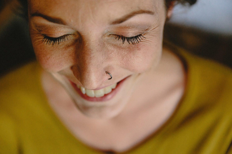 Nahaufnahme des Gesichtes der lachenden Braut mit Nasenpiercing beim Styling auf Hof Eggers