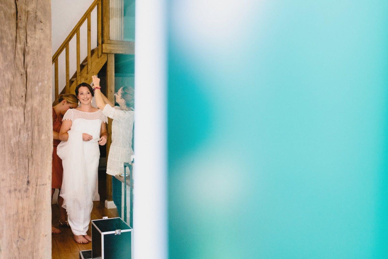Die Braut in ihrem Brautkleid wird von ihrer Trauzeugin und Friseurin gestylt Hochzeitsfotograf Hamburg