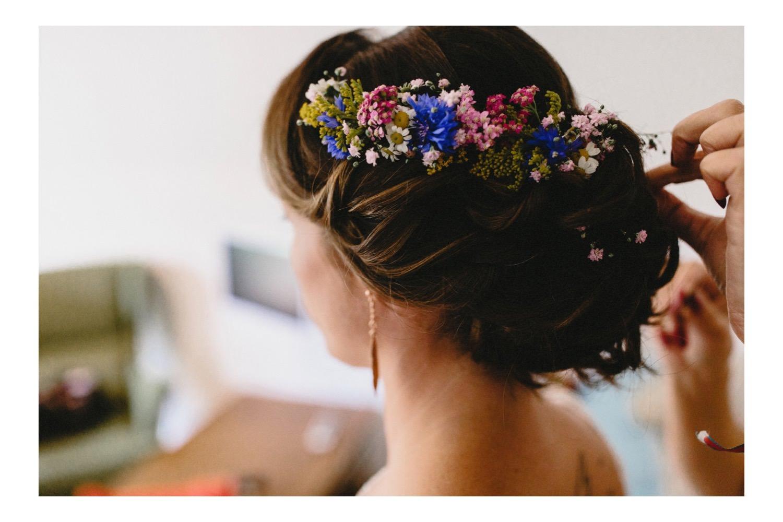 Die Braut vor der Hochzeit mit Blumenschmuck im frisierten Haar