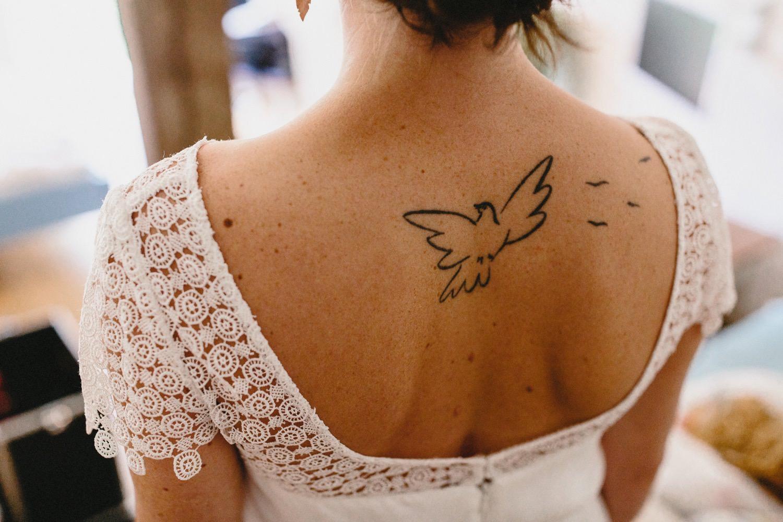 Nachaufnahme des Tattoos einer Friedenstaube auf dem Rücken der Braut im Brautkleid