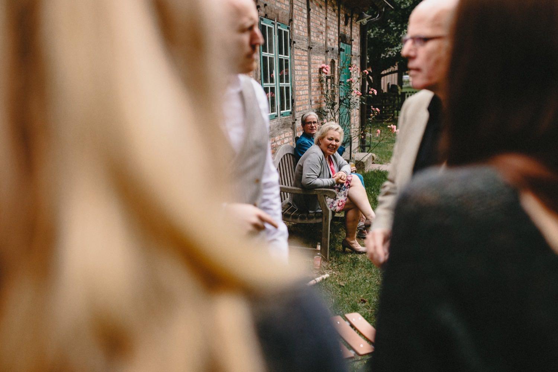 Die Gäste warten zusammen vor der Trauung vor einem Fachwerkhaus auf Hof Eggers