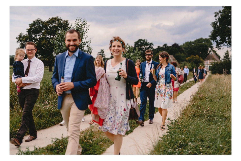 Die Gäste gehen zu Fuß vom Hof Eggers zur Trauung auf dem Feld unter einer großen Eiche