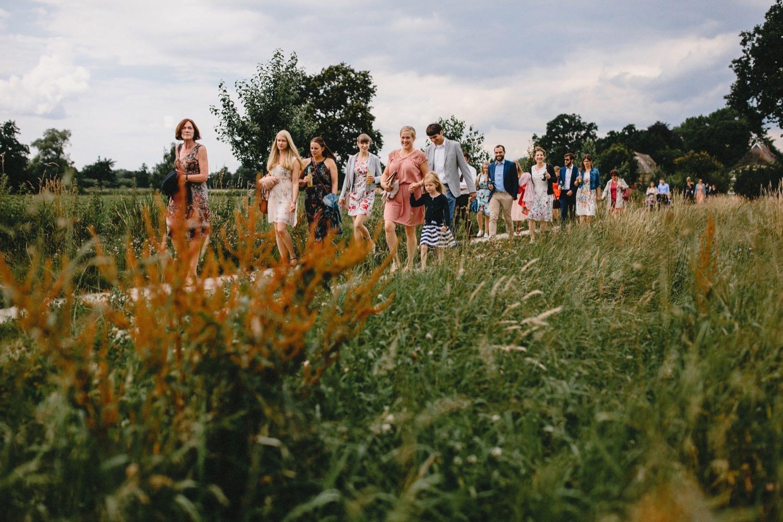 Gut gelaunte Hochzeitsgäste in schöner Kleidungauf dem Weg zur Trauung auf Hof Eggers in Hamburg Kirchwerder