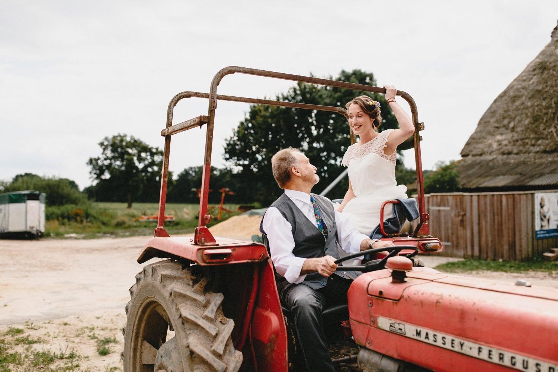 Hochzeit auf Hof Eggers der Brautvater fährt die Braut mit einem Trecker zur Trauung auf der Weide