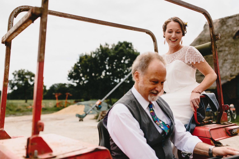 Der Vater startet den Trecker mit dem er die Braut zur Trauung auf Hof Eggers fährt Hochzeitsfotograf Till Gläser