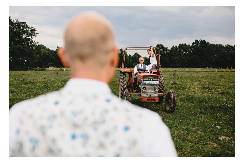 Der Bräutigam wartet auf die Braut, die von ihrem Vater mit dem Trecker zur Trauung gefahren wird
