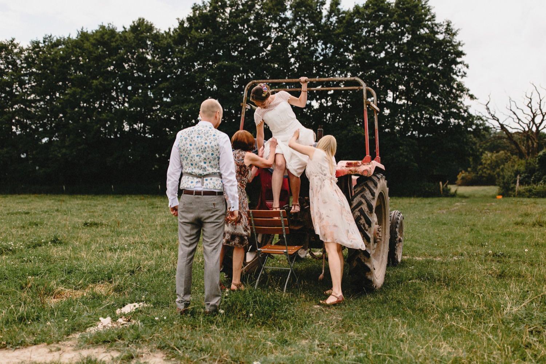 Die Braut steigt auf dem Feld vom roten Trecker und wird von ihrem Bräutigam in Empfang genommen