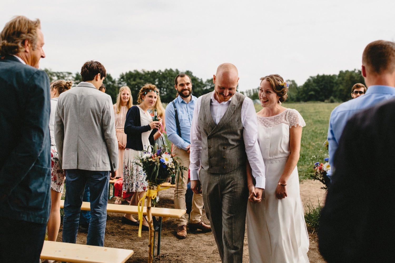 Braut und Bräutigam gehen durch die Stuhlreihen vorbei an ihren Gästen zum Ort der Trauung