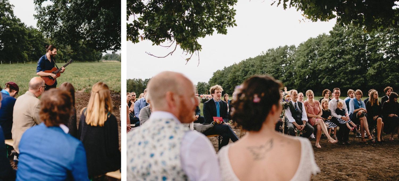 Die Gäste sitzen bei der weltlichen Hochzeitszeremonie auf Bänken und beteiligen sich mit musikalischen Beiträgen
