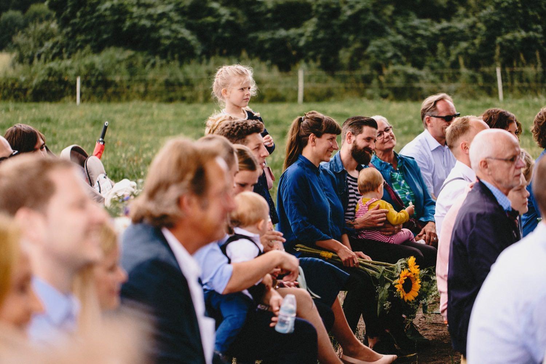 Glückliche Gäste mit Blumen in der Hand während der Trauung auf Hof Eggers