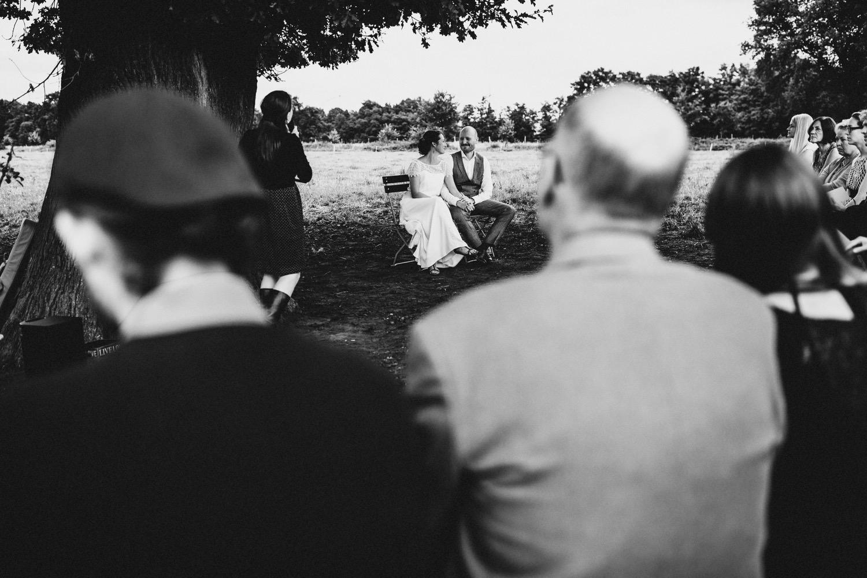 Das Brautpaar guckt sich tief in die Augen während der Trauung im Vordergrund sind die Gäste