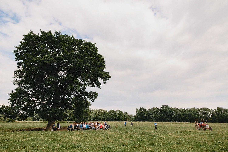 Weltliche Trauung unter einer großen Eiche auf einem weiten Feld auf dem Bio-Bauernhof Hof Eggers am Rand von Hamburg auf der rechten Seite steht ein Trecker