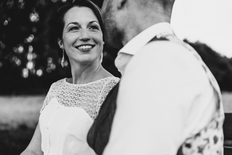 Die Braut im weißen Kleid und mit Nasenpiercing schaut dem Bräutigam in die Augen