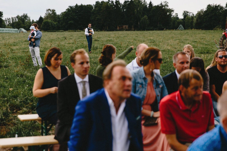 Väter mit ihren Kindern hinter den Gästen bei der Trauung auf Hof Eggers
