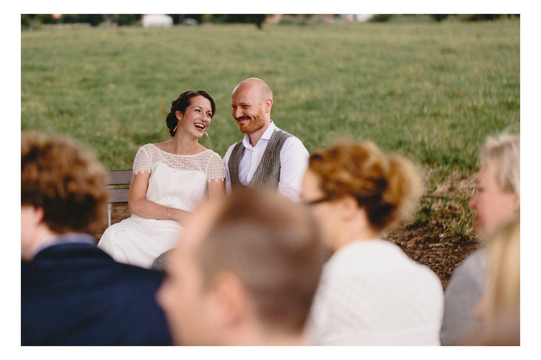Braut und Bräutigam lachen bei der weltlichen Trauung mit Gästen im Vordergrund