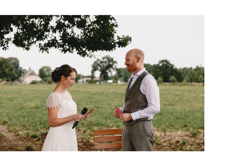 Braut in weißem Brautkleid und Bräutigam in einem Anzug von Herr von Eden geben sich das Eheversprechen auf Hof Eggers in Hamburg