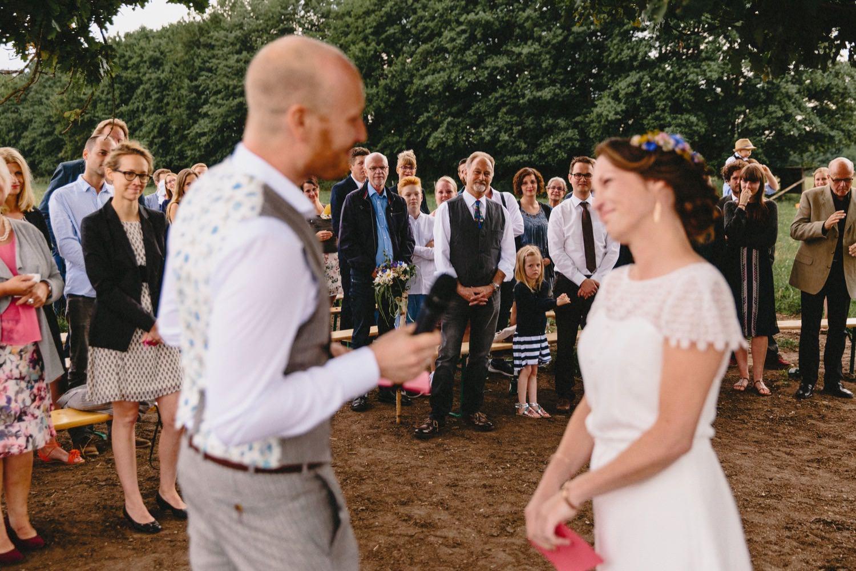 Die stehenden Gäste lauschen den Eheversprechen von Braut und Bräutigam bei der Hochzeit auf Hof Eggers