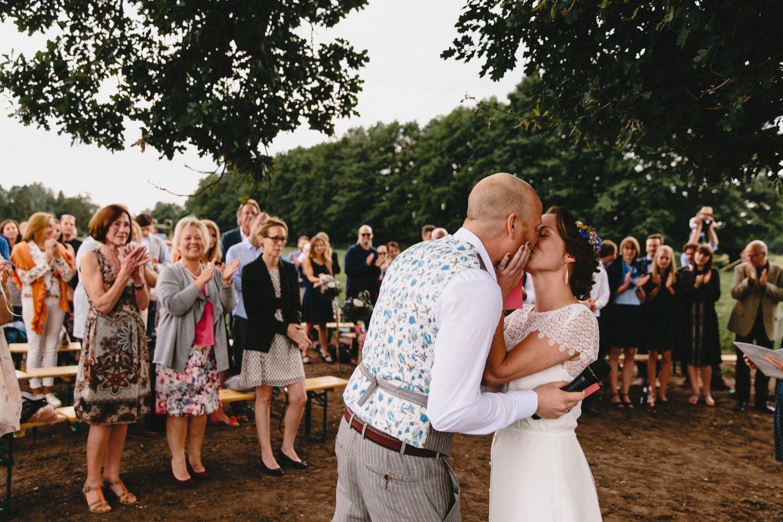 Braut und Bräutigam küssen sich in Anwesenheit der Gäste bei der weltlichen Trauungszeremonie