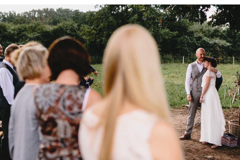 Der Bräutigam nimmt seine Braut bei der Trauung in den Arm, sie trägt ein weißes Brautkleid mit Spitze und der einen Anzug von Herr von Eden. Im Vordergrund sind die Gäste zu sehen
