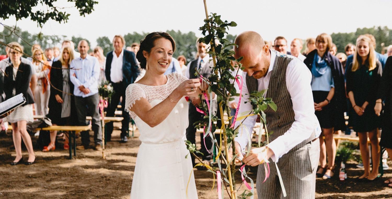 Braut und Bräutigam binden kleine Schleifen mit Wünschen an einen jungen Apfelbaum im Rahmen der weltlichen Trauungszeremonie unter freiem Himmel