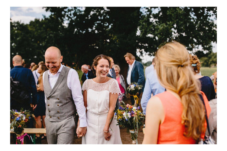 Das lachende Brautpaar, in weißem Kleid und grauem Hochzeitsanzug, gehen nach der freien Hochzeitszeremonie unter einer großen Eiche durch die Reihen der Gäste
