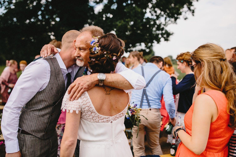 Der Brautvater umarmt das Brautpaar, die Braut hat Blumen im Haar, auf der rechten Seite steht ein Hochzeitsgast in einem roten Kleid