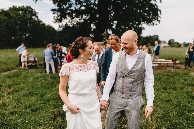 Das Brautpaar zieht nach der freien Hochzeitszeremonie unter der großen Eiche auf dem großen Feld gemeinsam aus und lacht sich dabei an