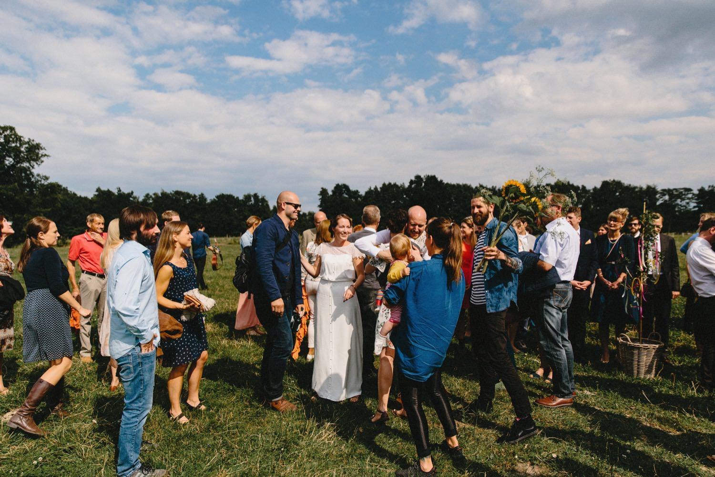 Eine große Gruppe von Gästen bei der Gratulation auf der Weide bei strahlendem Sonnenschein und blauem Himmel mit ein paar kleinen Wolken