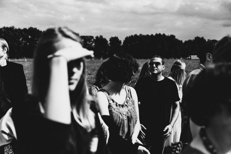 Gäste der Hochzeit auf dem Hof Eggers bei der Gratulation auf der Weide in strahlendem Sonnenschein in Schwarz-Weiß