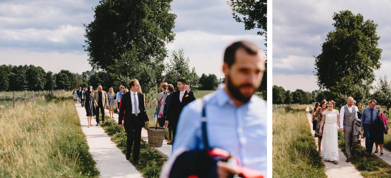 Die Gäste und das Brautpaar laufen nach der freien Trauungszeremonie auf der Weide über den Feldweg zurück zum Hof Eggers