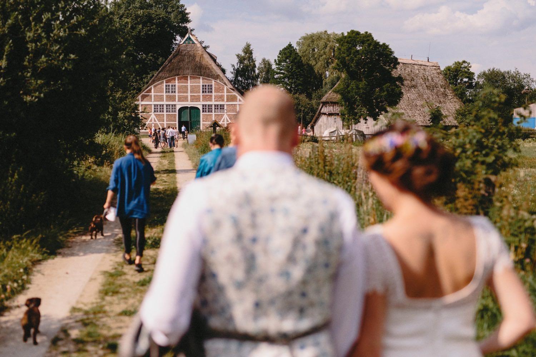 Das Brautpaar geht auf dem Feldweg zurück zum Hof Eggers im Hintergrund sieht man die alte denkmalgeschützte Fachwerkscheune und die andere Gebäude vom Hof