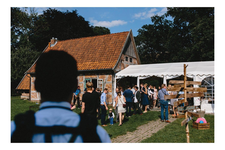 Gäste beim Hochzeitsempfang auf dem Hof Eggers mit der Festscheune und einem Partyzelt bei strahlendem Sonnenschein