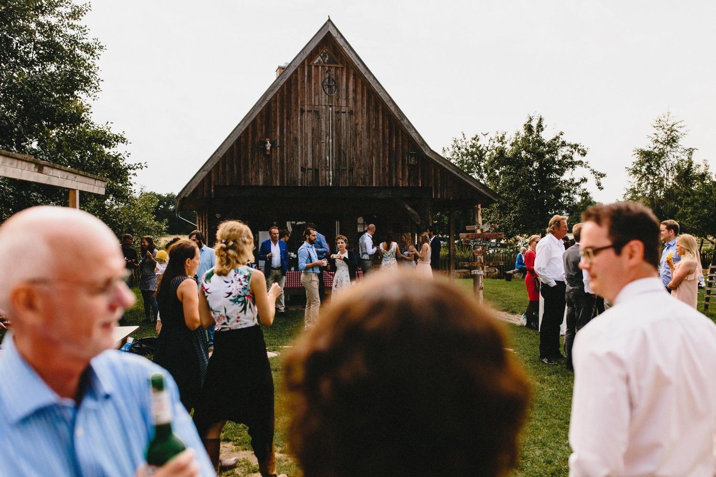 Gäste stehen beim Hochzeitsempfang verteilt auf dem Hof Eggers und genießen den Sonnenschein