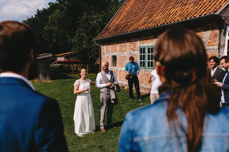 Das Brautpaar hält eine Ansprache an die Gäste im Hintergrund ist die Fachwerkpartyscheune zu sehen in der später die Hochzeitsparty stattfindet