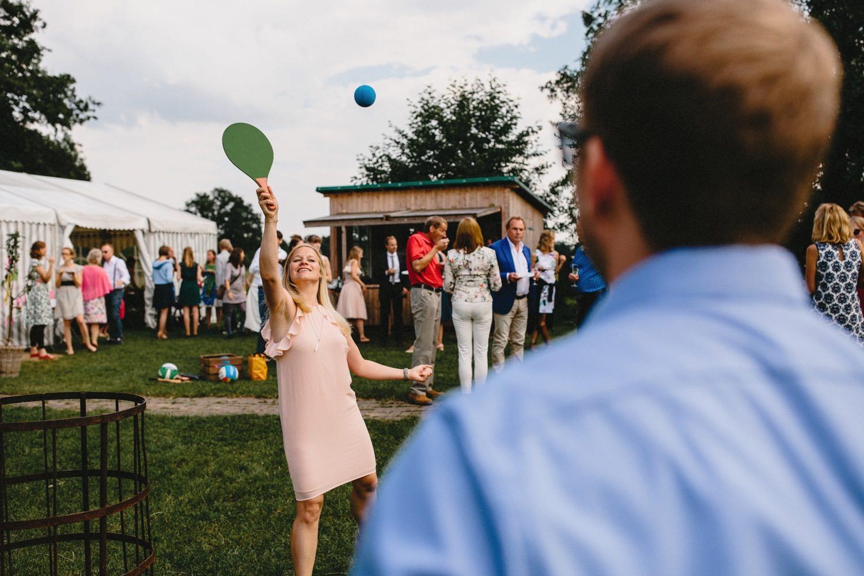 Zwei Gäste spielen Beach-Ball beim Hochzeitsempfang, die Frau trägt ein rosa Kleid und der Mann ein blaues Hemd im Hintergrund sind die anderen Hochzeitsgäste des Empfanges zu sehen