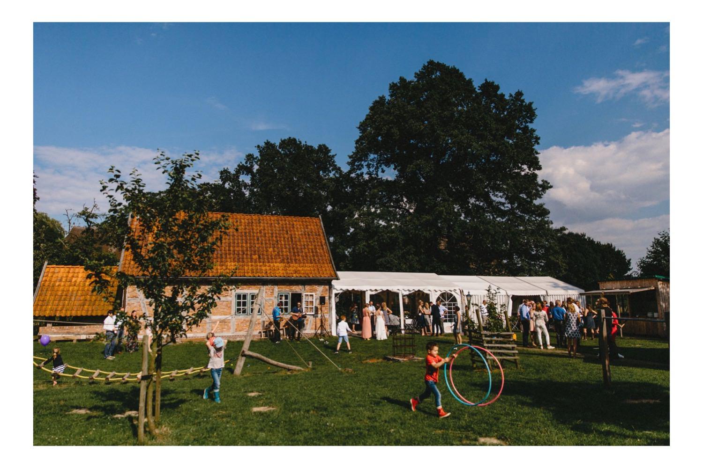 Ein Überblick über den Hof Eggers und die Gäste beim Hochzeitsempfang links ist die Fachwerkscheune und rechts das Partyzelt