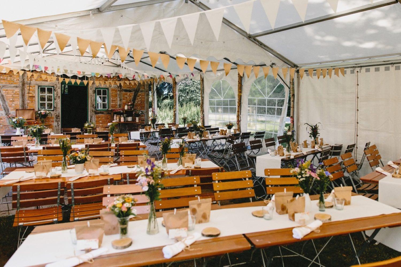 Das eingedeckte Partyzelt mit Tischdekoration, Blumendeko und Parygirlanden
