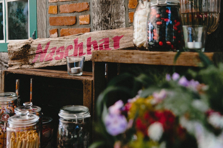 Die Candy-Bar vor der Fachwekmauer im Partyzelt der Hochzeit auf Hof Eggers
