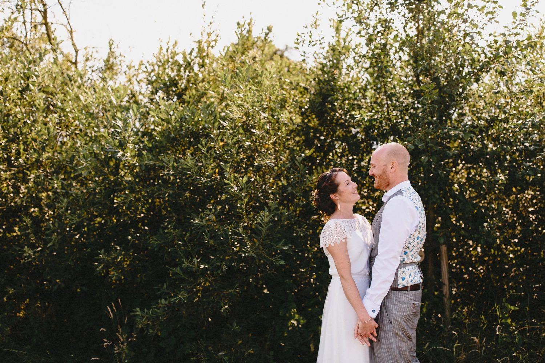 Portraitfoto des Brautpaares vor einem Busch im Gegenlicht, beide gucken sich in die Augen und lachen sich an