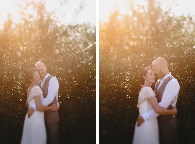 Gegenlichtportrait des kuschelnden Brautpaares vor einem Strauch mit Sunflair