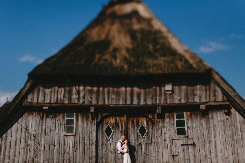 Braut in weißem Kleid und Bräutigam im grauen Hochzeitsanzug stehen vor einer alten Bauernscheune mit Reetdach vor blauem Himmel