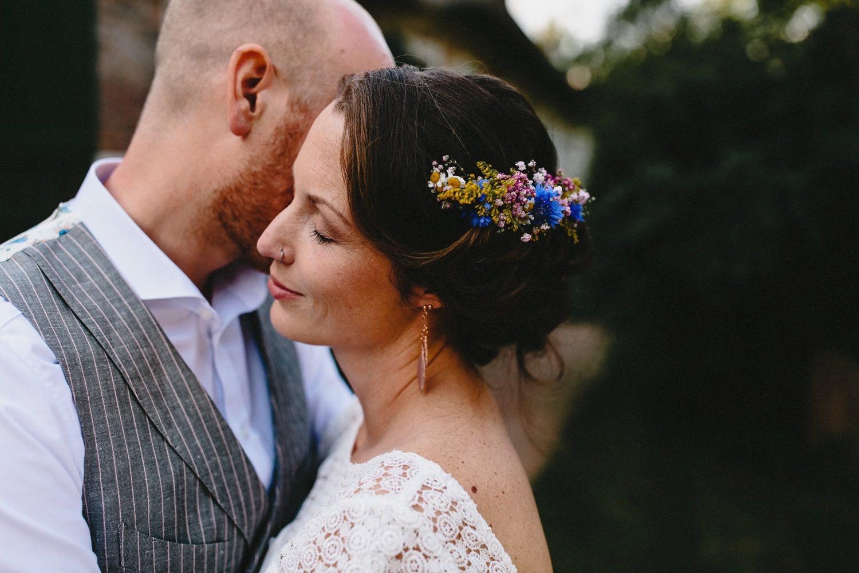 Nahaufnahme des innig kuschelnden Brautpaares auf dem Hof Eggers in Hamburg, die Braut trägt Blumenschmuck im Haar und der Bräutigam trägt einen grauen Hochzeitsanzug von Herr von Eden