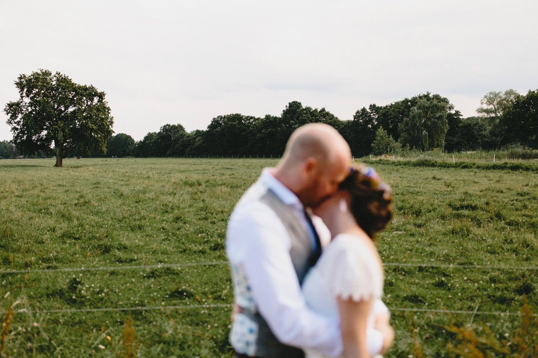 Das unscharfe Brautpaar vor einer leeren Weide, im Hintergrund ist die große Eiche zu sehen, unter der ihre weltliche Trauung stattfand