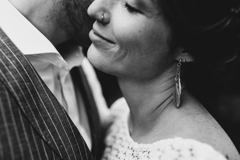 Portraitfoto des kuschelnden Brautpaares, sie trägt einen Ohrring in Form von Federn und lehnt sich an ihrem Bräutigam an